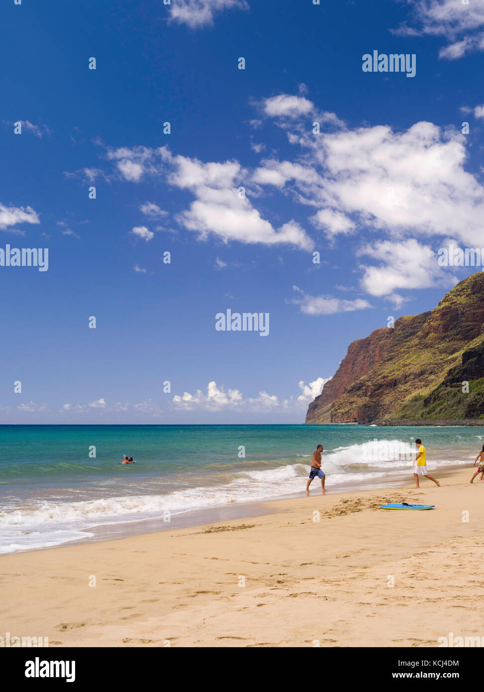 People enjoying the surf at Polihale State Park and its barking sands on the west coast of Kauai, Hawai'i. Stock Photo