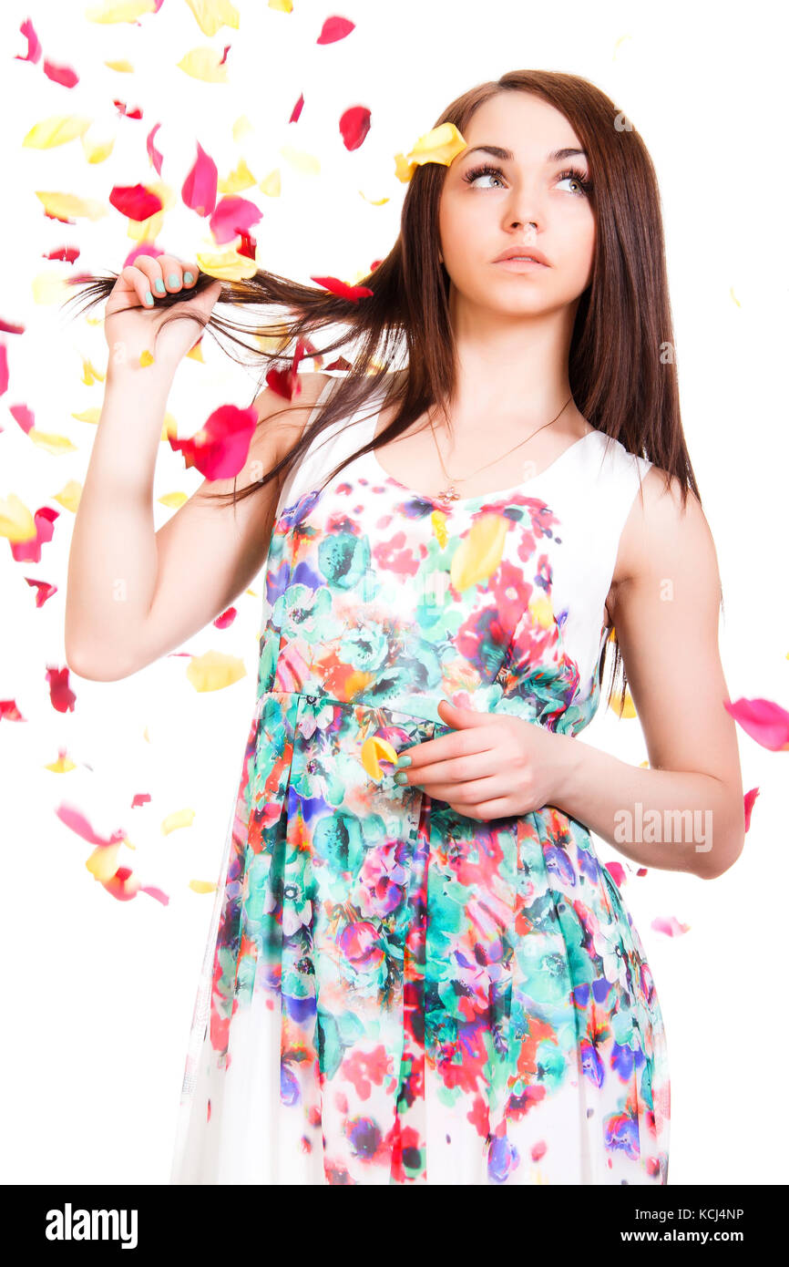 Portrait of a pretty young woman in a bright dress isolated over white background with pink and yellow falling petals - Stock Image