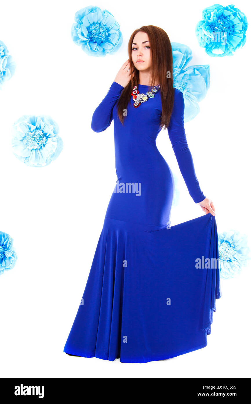 Beautiful young woman in a long blue evening dress at the background of the cyan flowers - Stock Image
