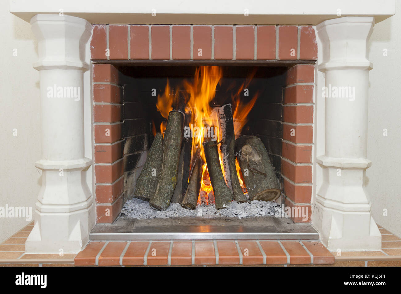 White fireplace with a burning fire - Stock Image