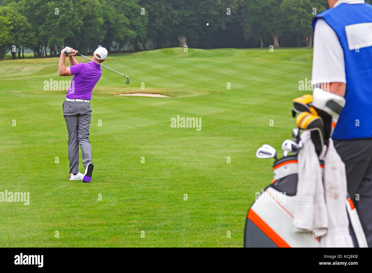 A professional golfer playing an iron shot on a par 4 with his caddy looking on. - Stock Image
