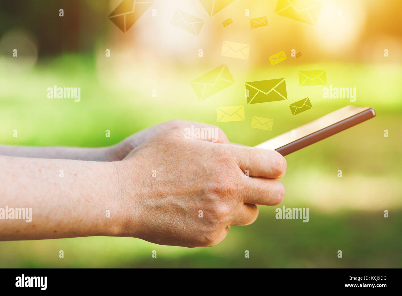 Mobile phone communication concept with female hands using smartphone app and envelopes as outgoing e-mail or text - Stock Image