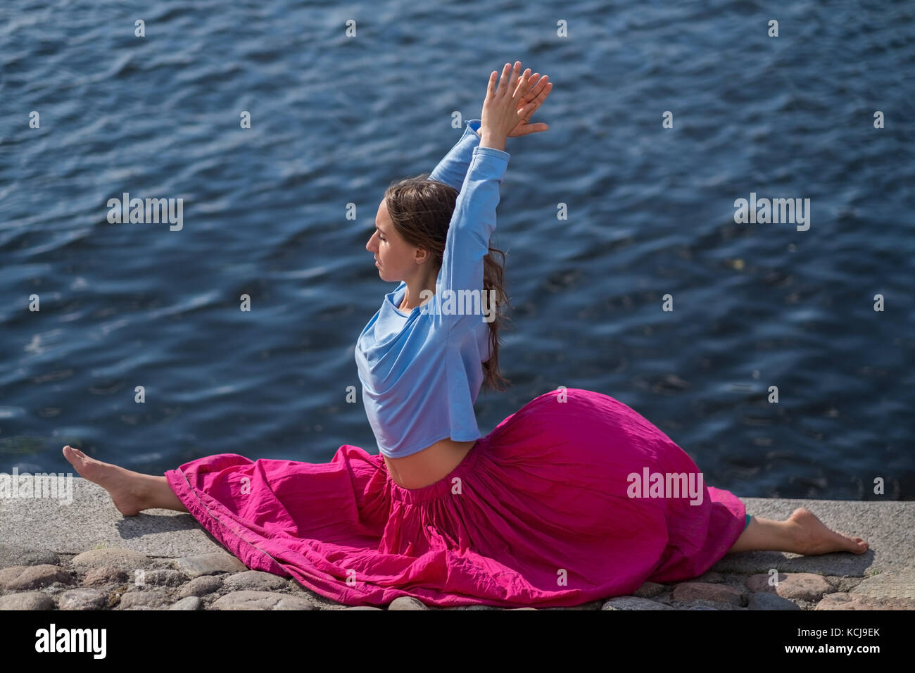 Sporty fit caucasian woman doing asana hanumanasana pose posture in nature. - Stock Image