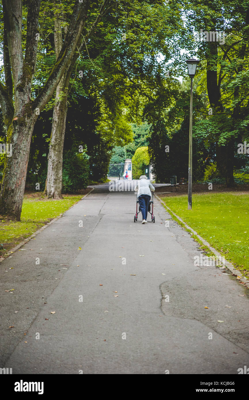 An old woman walking alone - Stock Image
