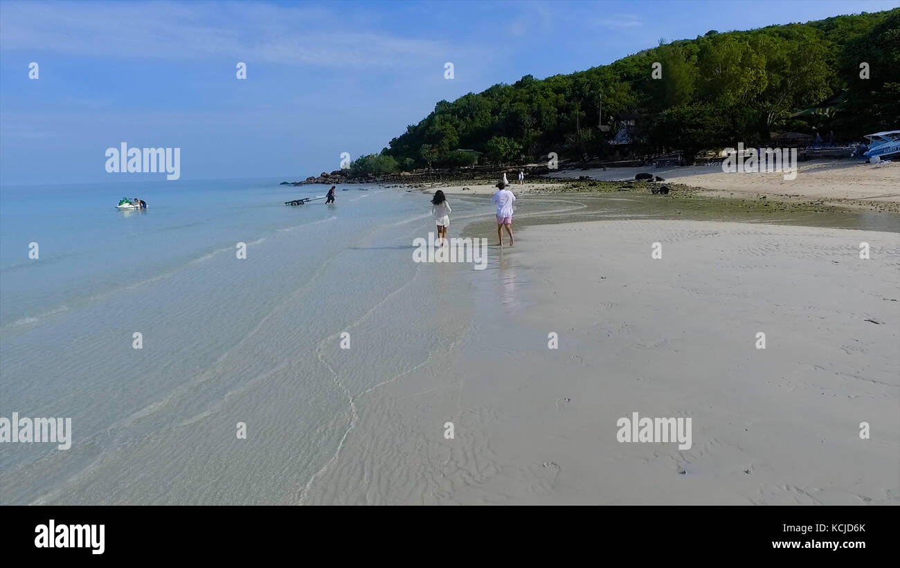 Happy couple running on the beach. Happy couple running on a tropical beach in the ocean at sunset. Couple running - Stock Image