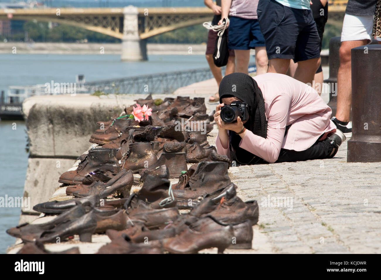 The Shoes on the Danube Bank memorial in Budapest on a sunny day with a tourist taking pictures. - Stock Image