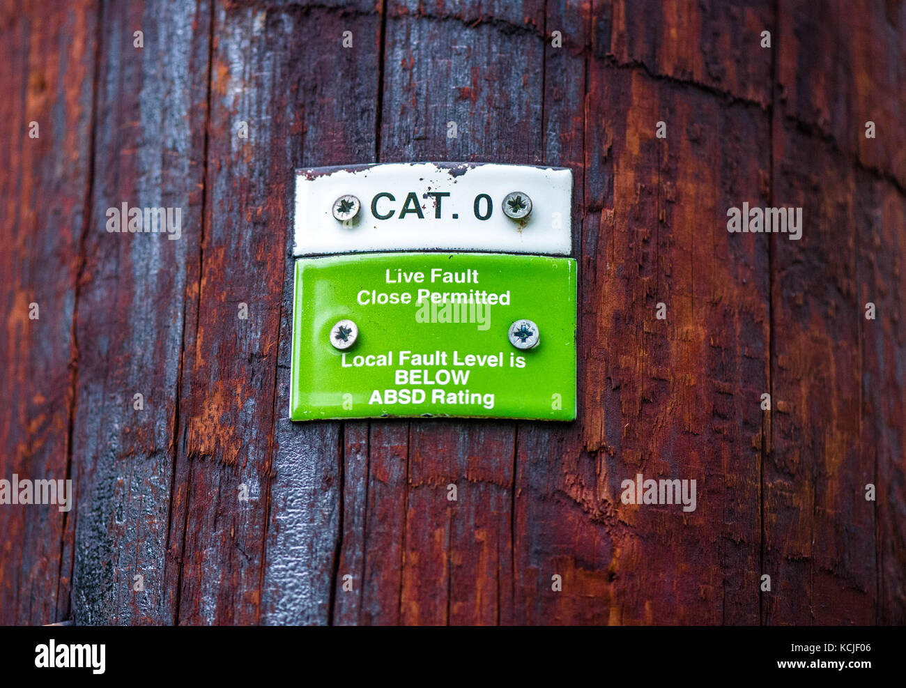 Category 0 and Live Fault label attached to a wooden 33KV over head electrical distribution pole. - Stock Image
