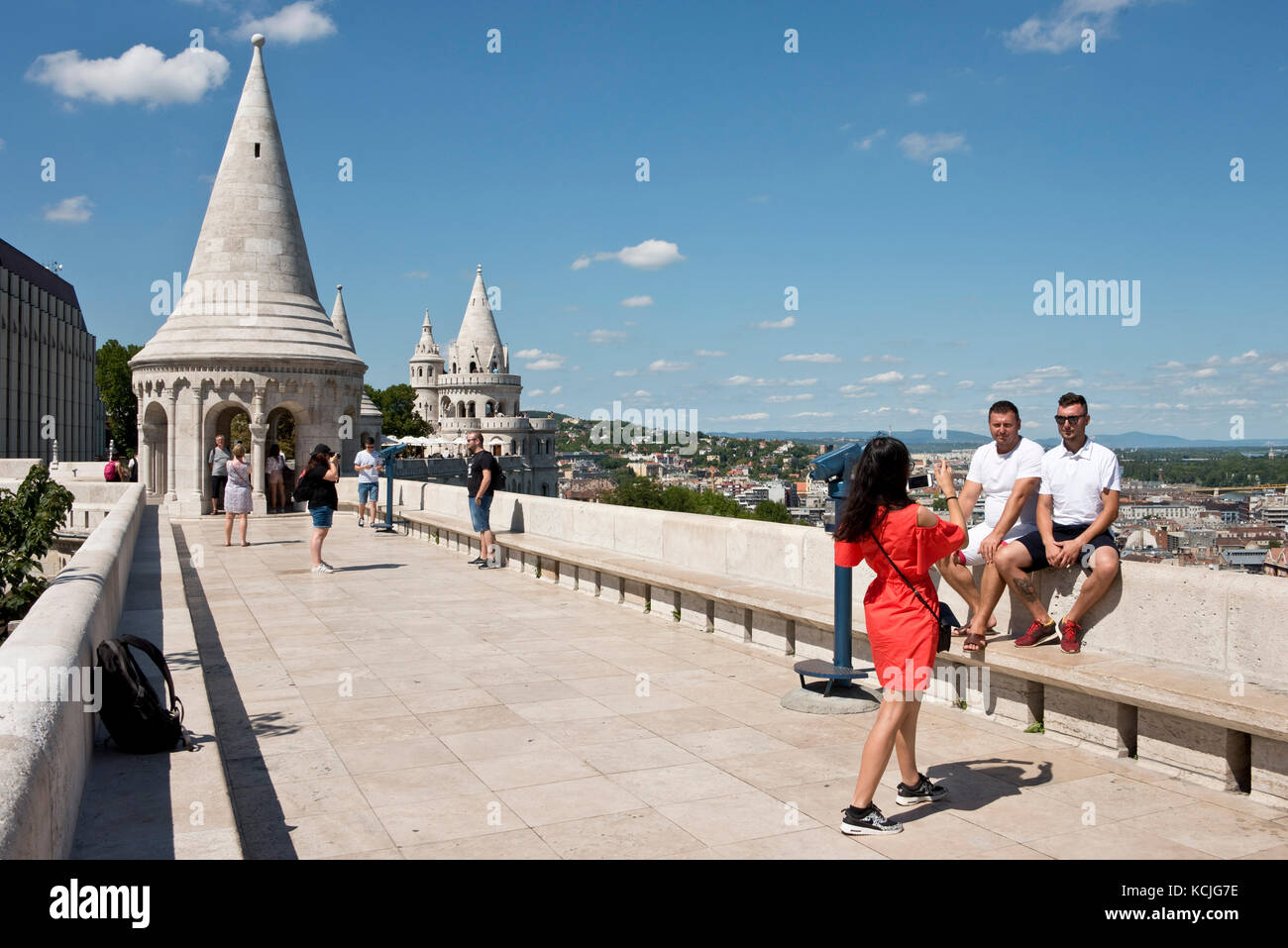 Tourists on the walls of the Fisherman's Bastion in Budapest looking at the view and taking photographs pictures - Stock Image