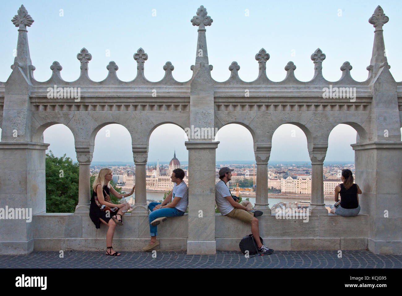 Four 4 people, two 2 couples tourists on the walls of the Fisherman's Bastion admiring the view of Budapest - Stock Image