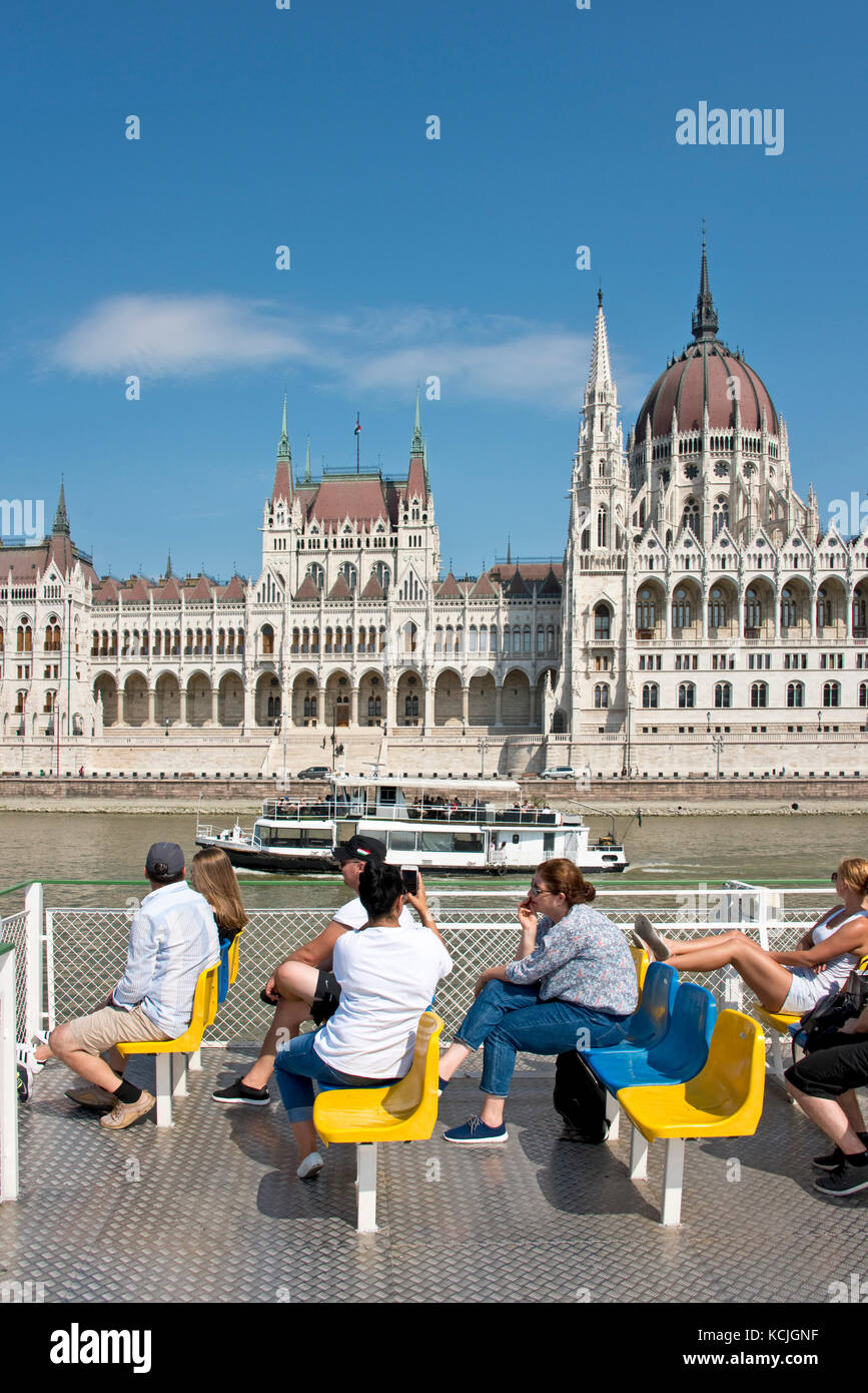 Tourists enjoying a river cruise on the Danube as it passes by the Hungarian Parliment Building on a sunny day with Stock Photo