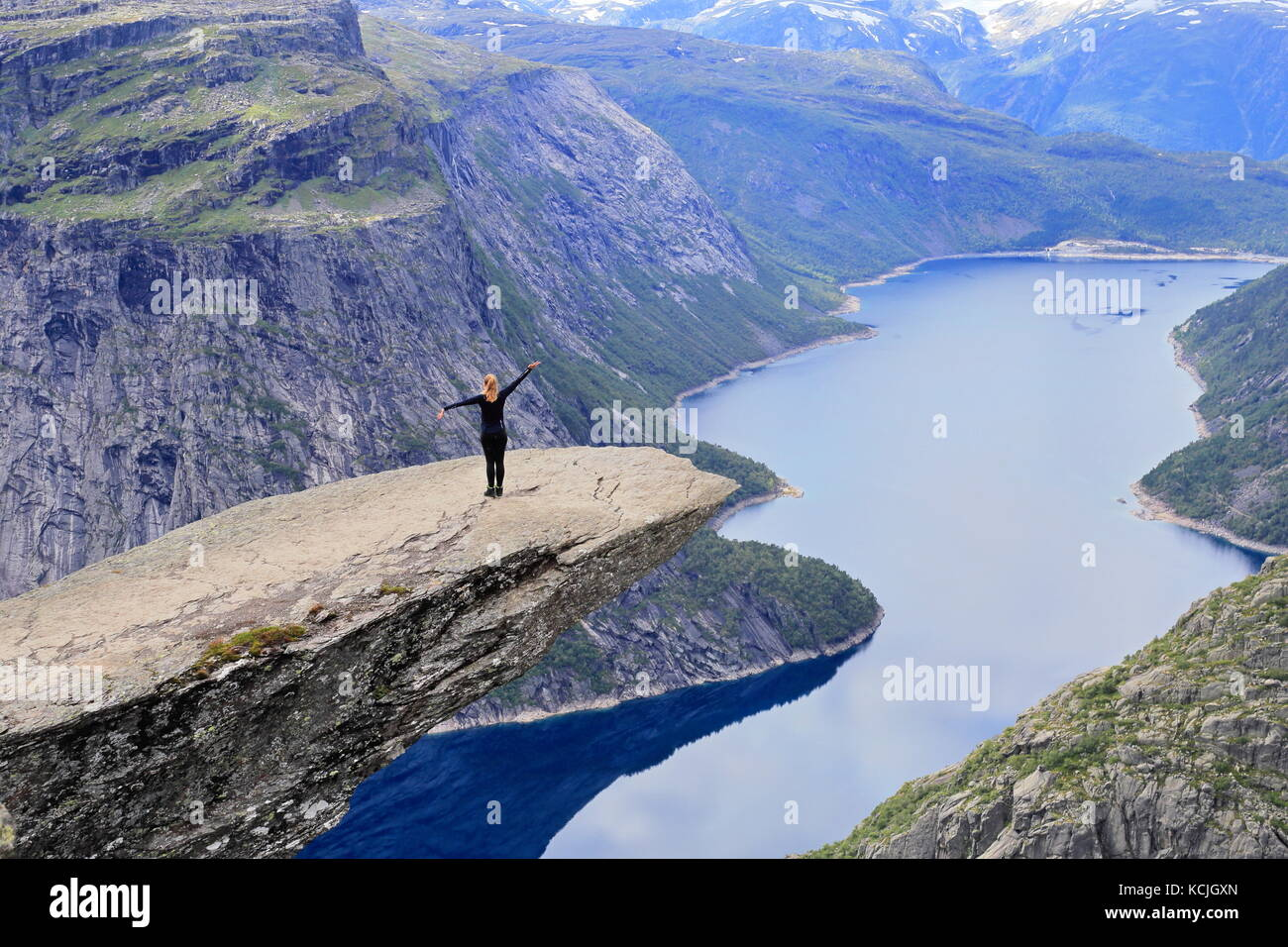 Woman Hiker posing and enjoying view from Trolltunga rock formation in Norway - Stock Image