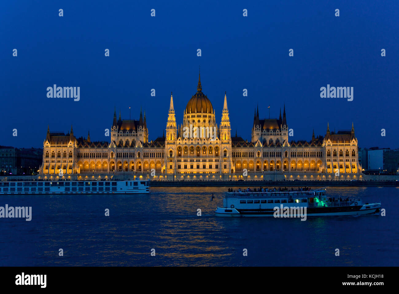 An evening nighttime view of the Hungarian Parliment Building on the Danube river in Budapest with a tourist river - Stock Image
