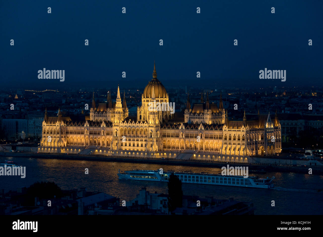 An aerial cityscape evening nighttime view of the Hungarian Parliment Building in Budapest with a tourist river Stock Photo