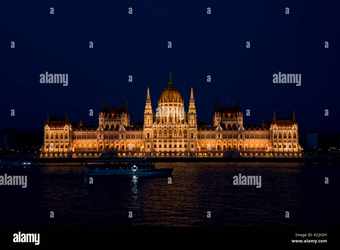 An evening nighttime view of the Hungarian Parliment Building on the Danube river in Budapest with a tourist river Stock Photo