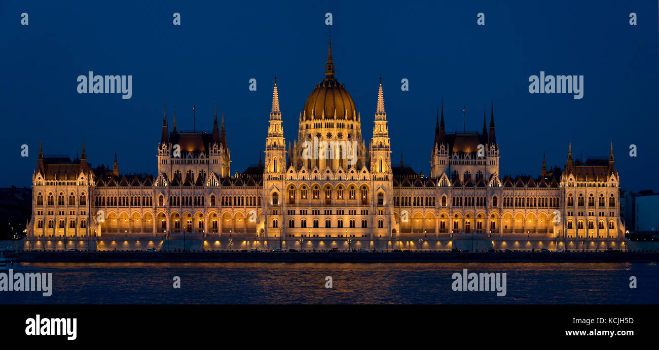 A 2 picture stitch evening nighttime view of the Hungarian Parliament Building on the Danube river in Budapest. - Stock Image