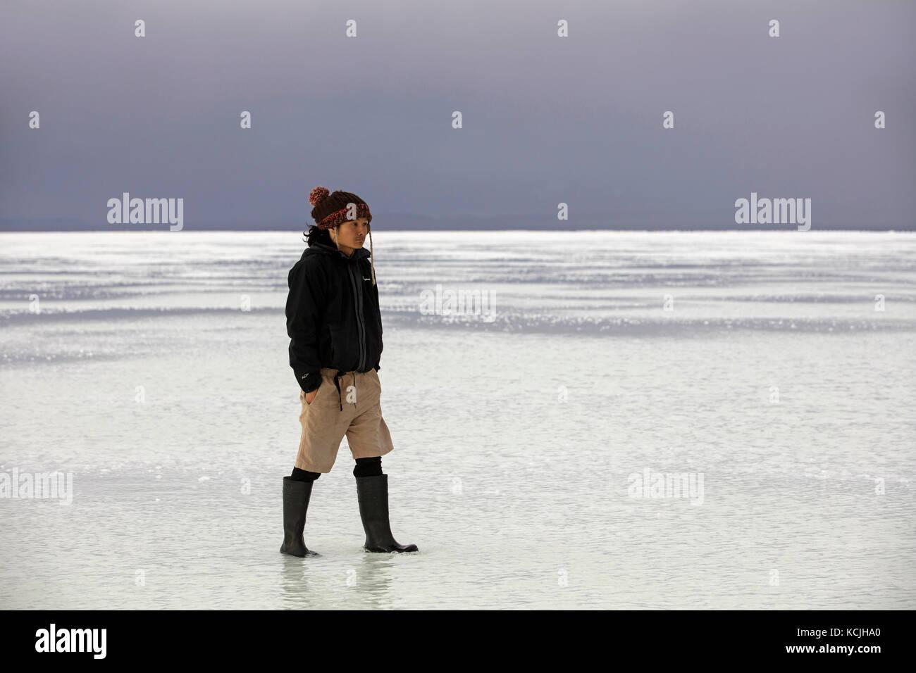 Tourist walking on the Salar de Uyuni / Salar de Tunupa covered with water, world's largest salt flat, Daniel - Stock Image