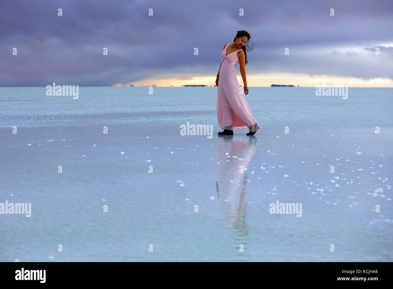 Korean tourist posing on the Salar de Uyuni / Salar de Tunupa covered with water, world's largest salt flat, - Stock Image