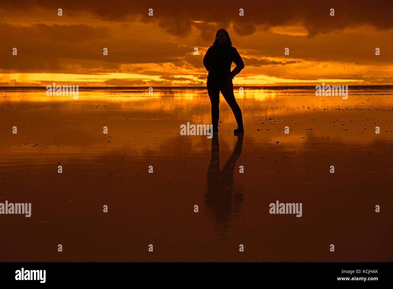Silhouette of tourist posing on the Salar de Uyuni / Salar de Tunupa at sunset, world's largest salt flat, Daniel - Stock Image