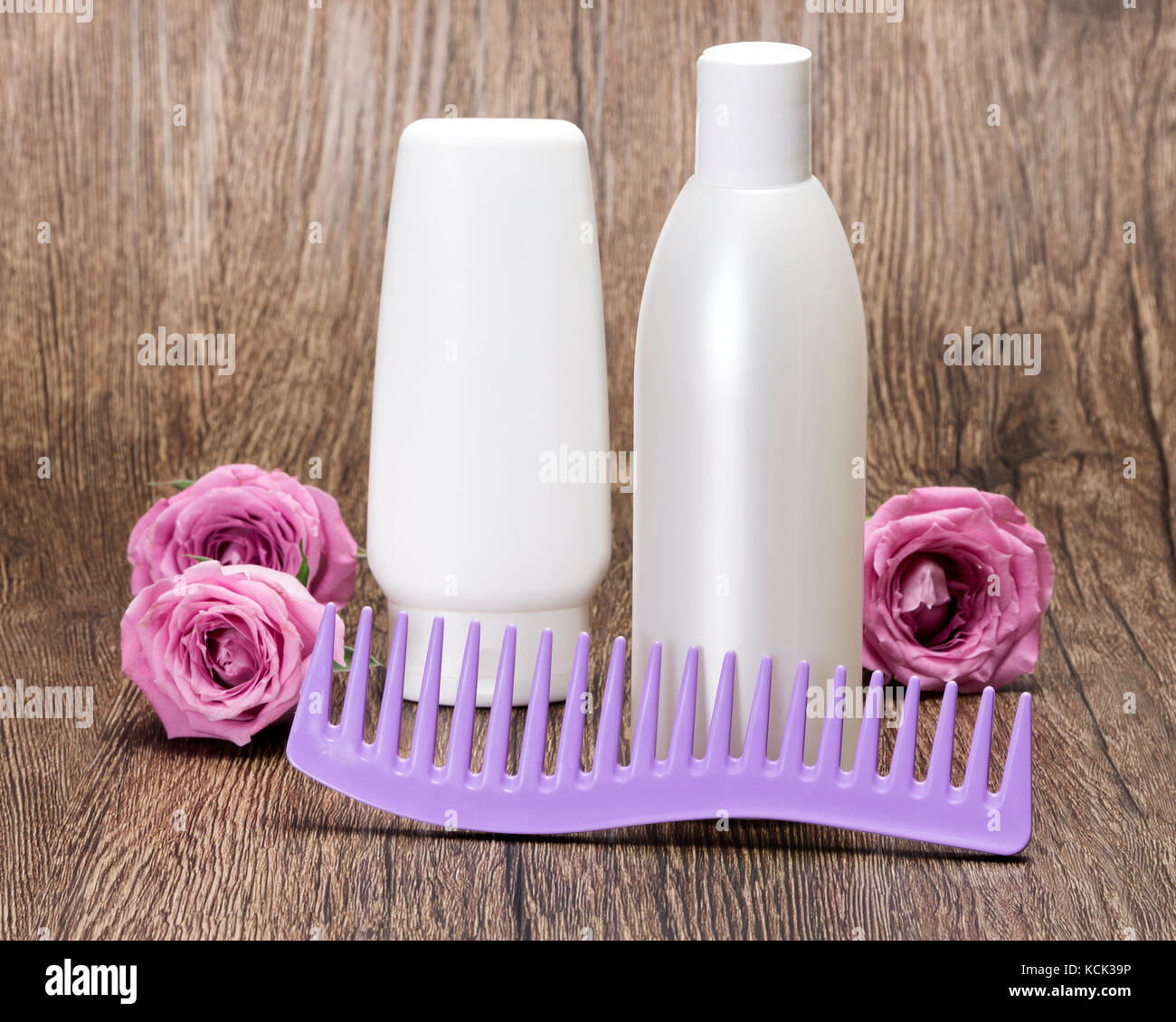 Hair care and styling cosmetics. Hair beauty products and comb with roses on wooden surface Stock Photo