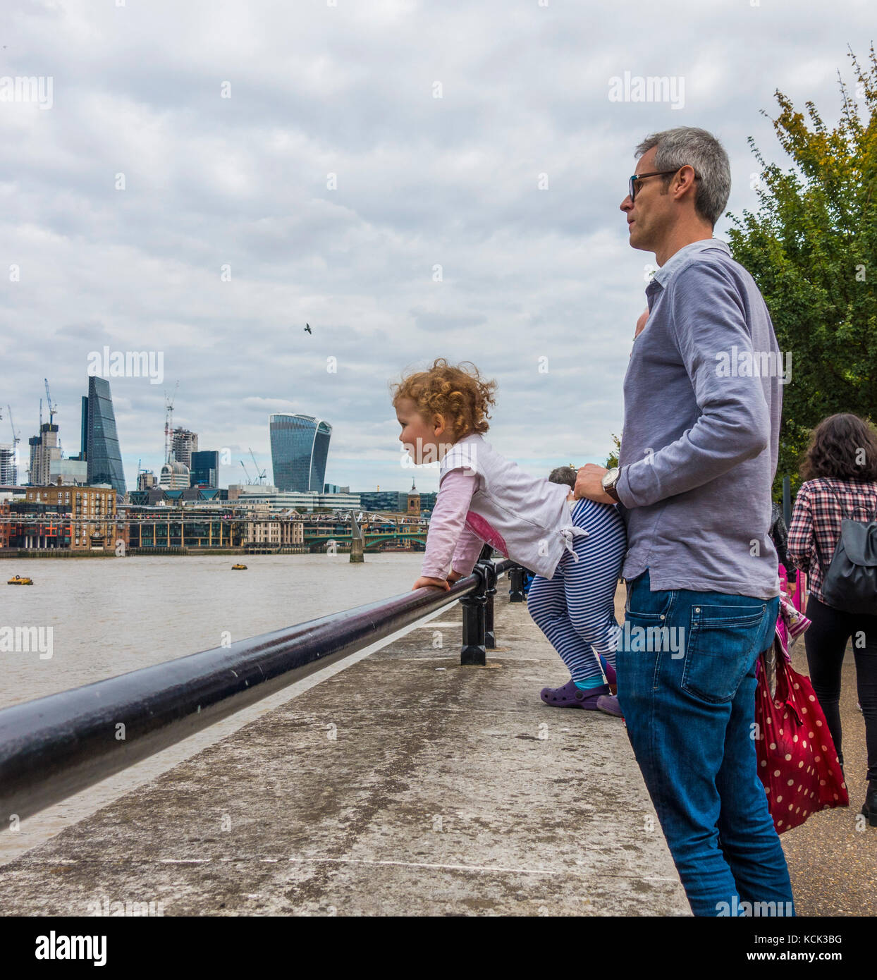 A middle aged father holding his curly haired young daughter, grasping a safety rail, overlooking the River Thames, - Stock Image