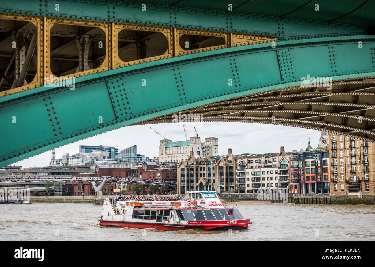 Arched section of Southwark Bridge on Bankside, with a busy cruise boat passing on the River Thames and riverside - Stock Image