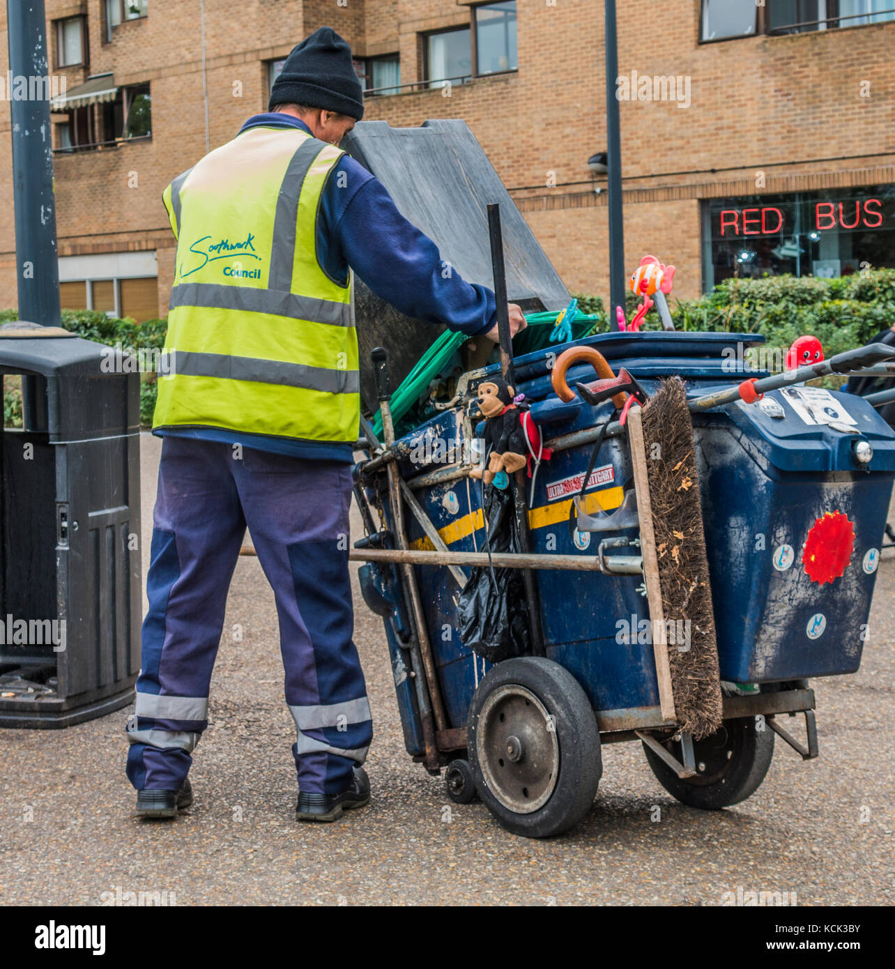 London worker - Borough of Southwark male council refuse collector, emptying a bin into a push cart with attached Stock Photo