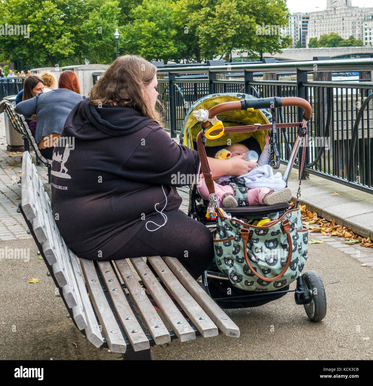 Overweight, single parent, teenage mother, sitting on a wooden bench, bottle feeding milk to her baby in a pushchair, - Stock Image