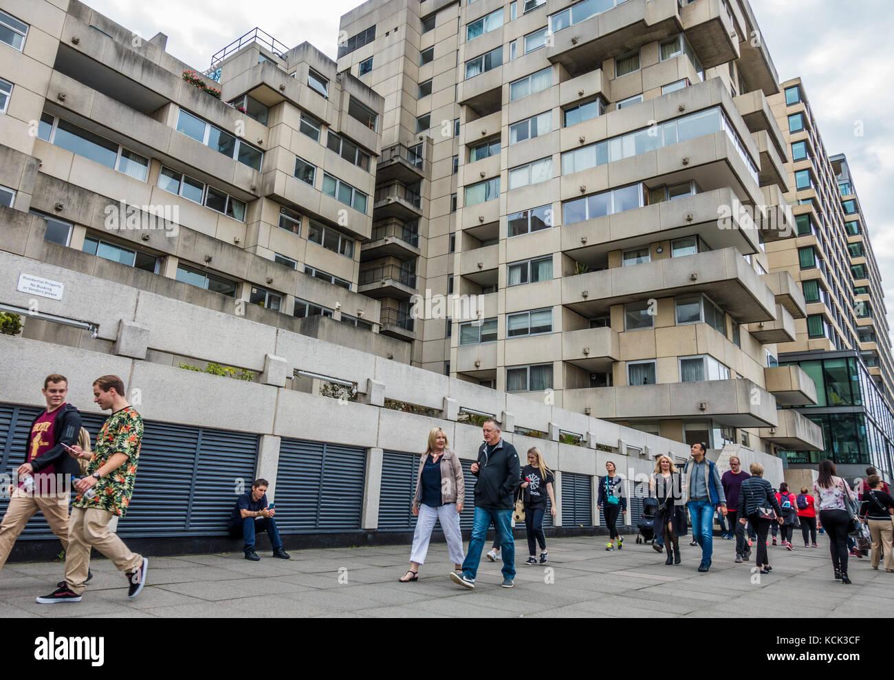 People walking past old concrete apartment blocks, facing the River Thames on Bankside, London, England, UK. - Stock Image