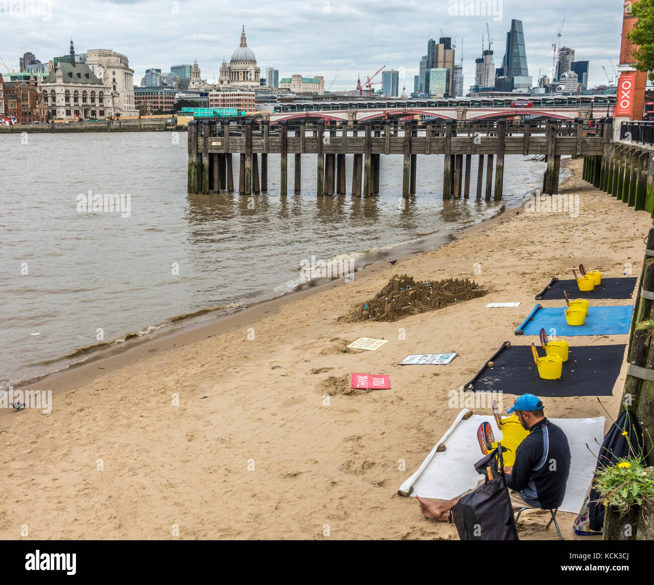Sandcastle sculpture, with the sculptor seeking donations, on an urban beach with city view on  the River Thames - Stock Image