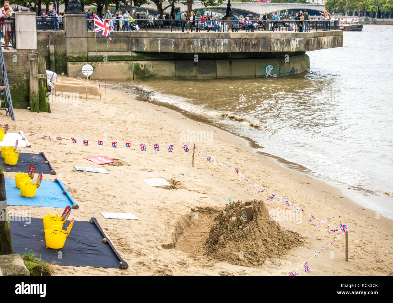 Sandcastle sculpture, with the sculptor seeking donations, on an urban beach next to a busy South Bank of the River - Stock Image