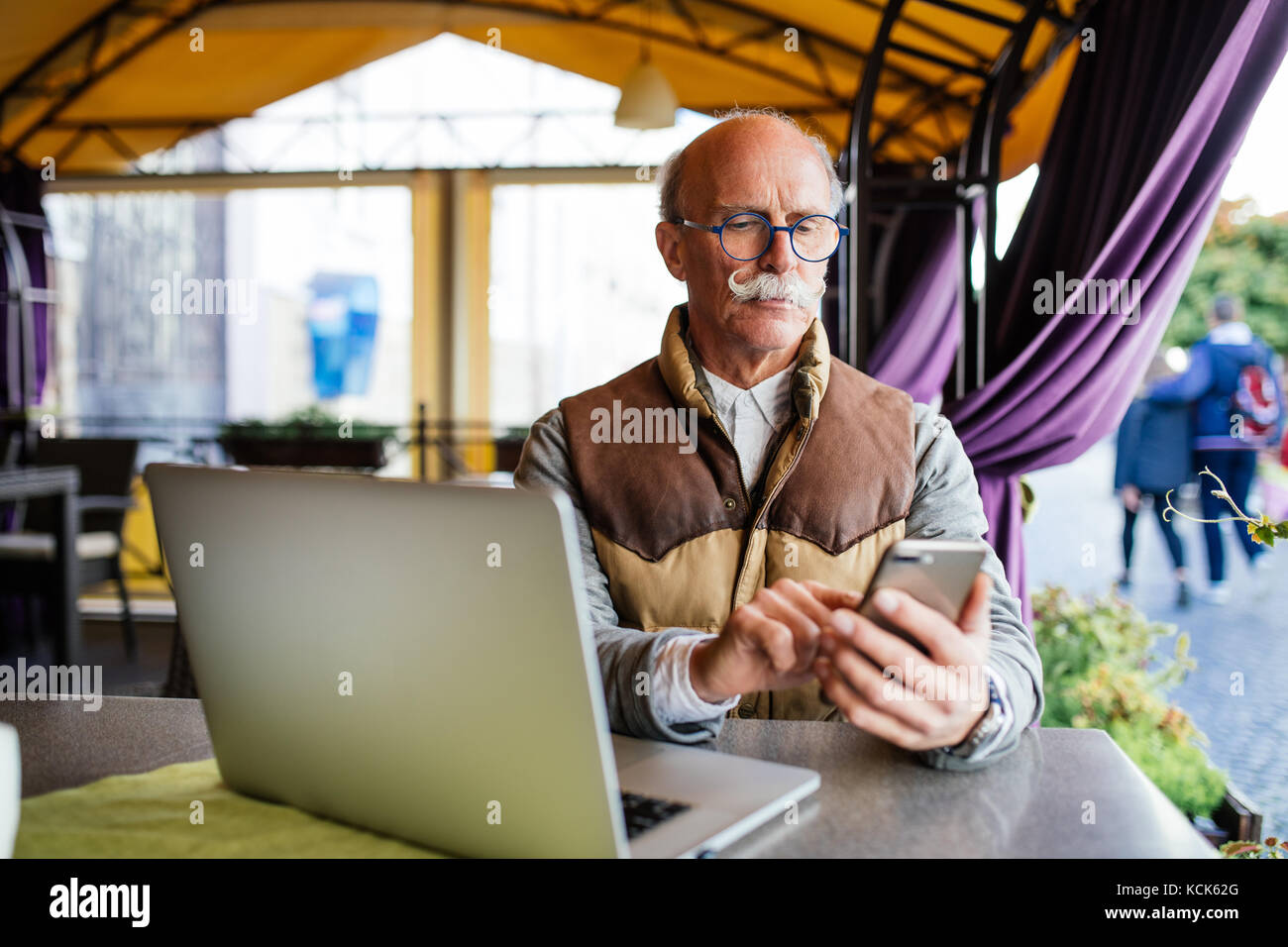 Old senior businessman in suit and tie with laptop computer and smartphone, sitting in city cafe house - Stock Image