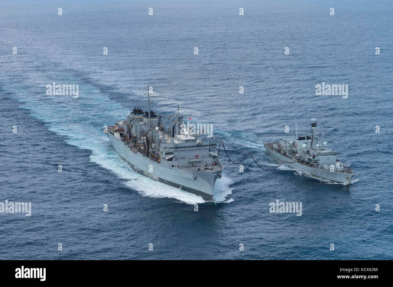 The U.S. Navy Supply-class fast combat support ship USNS Supply (left) steams in formation with the British Royal - Stock Image
