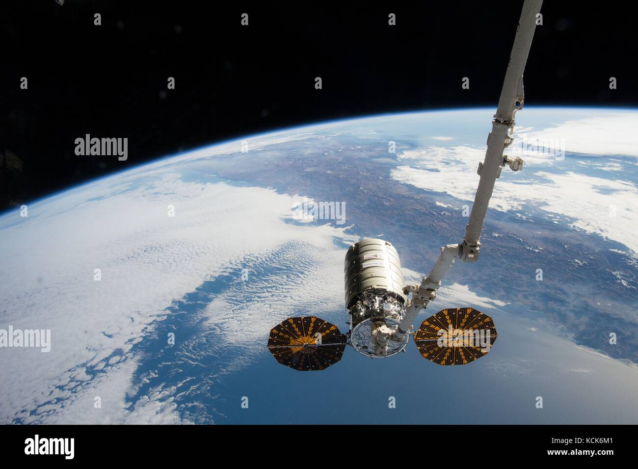 The NASA International Space Station Canadarm2 robotic arm grabs the Orbital ATK Cygnus cargo spacecraft after being - Stock Image