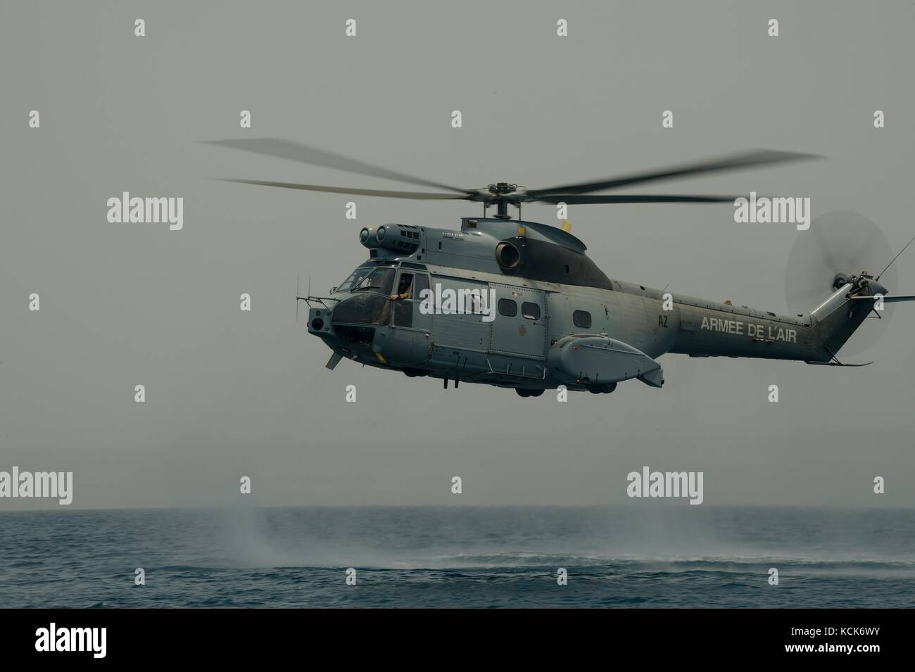 A French Air Force Aerospatiale SA 330 Puma utility helicopter hovers over the ocean during a water exercise with - Stock Image