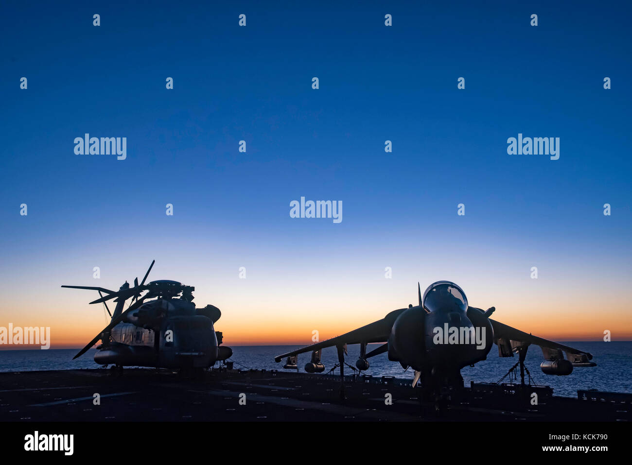 A U.S. Marine Corps CH-53E Super Stallion helicopter (left) and an AV-8B Harrier II ground-attack aircraft sit on - Stock Image