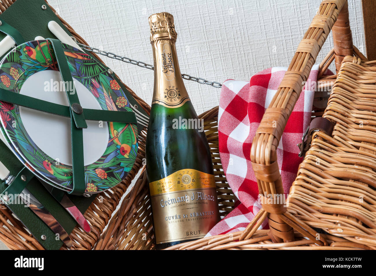 Picnic preparations with Cremant d'Alsace bottle in picnic hamper basket with typical chequered tablecloth - Stock Image