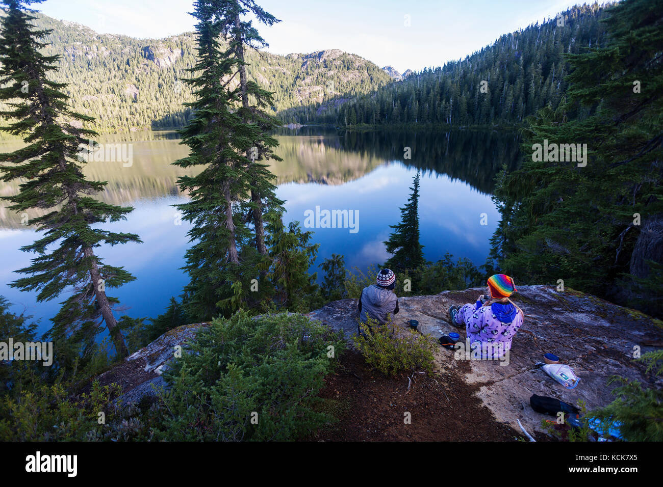 Two girlfriends, camping at Bedwell Lake enjoy an early morning coffee.  Strathcona Park, Central Vancouver Island, - Stock Image
