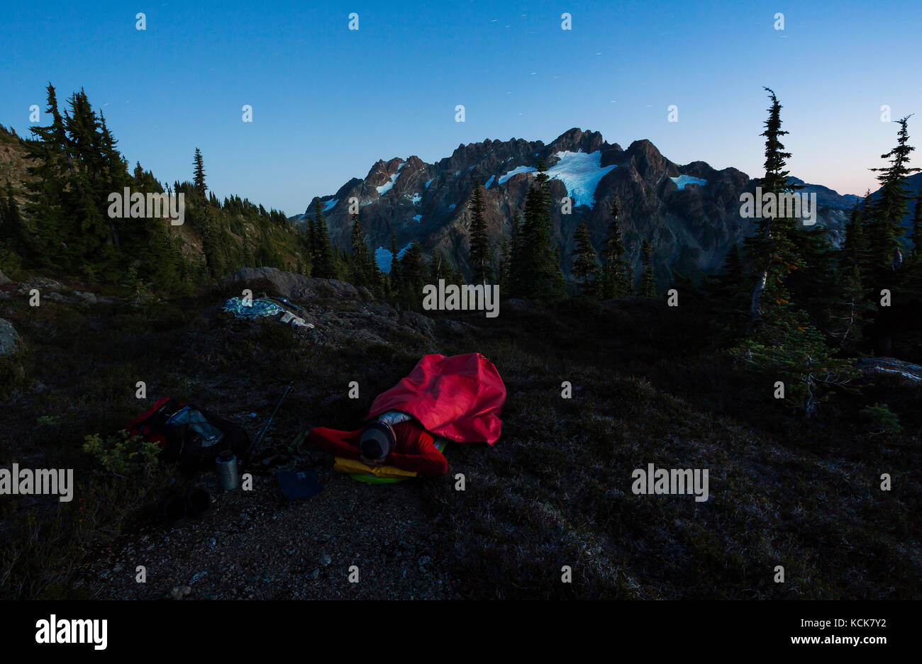A lone hiker looks up to the Septimus/Rousseau massif and it's hanging glacier while camping overnight on the - Stock Image
