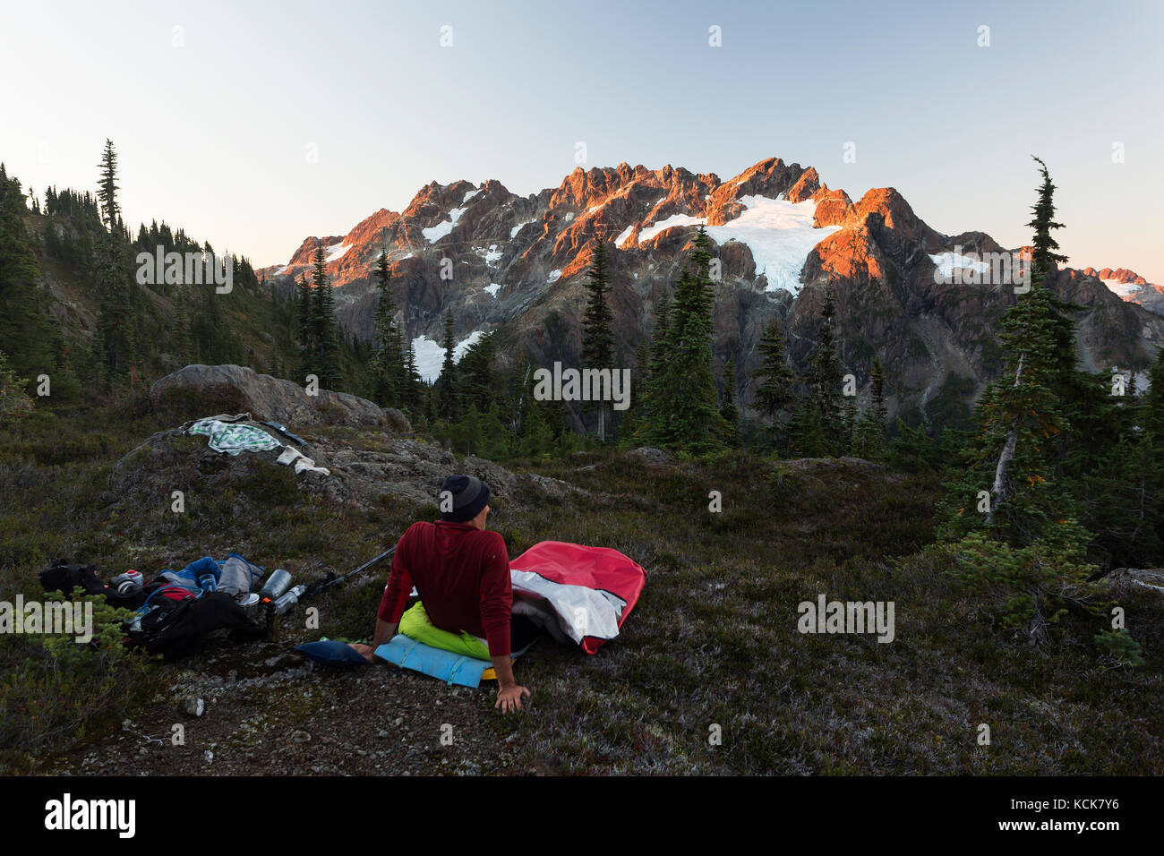 A lone hiker wakes up to early morning light scupting across the Septimus/Rousseau massif while hiking on the Flower - Stock Image