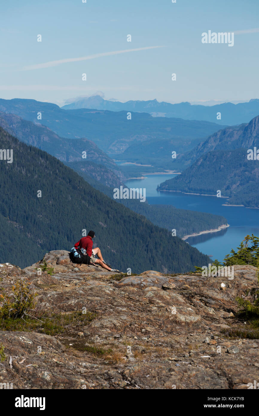A lone male hiker relaxes at a viewpoint on the Flower Ridge trail overlooking Buttle Lake in Strathcona Park.  - Stock Image