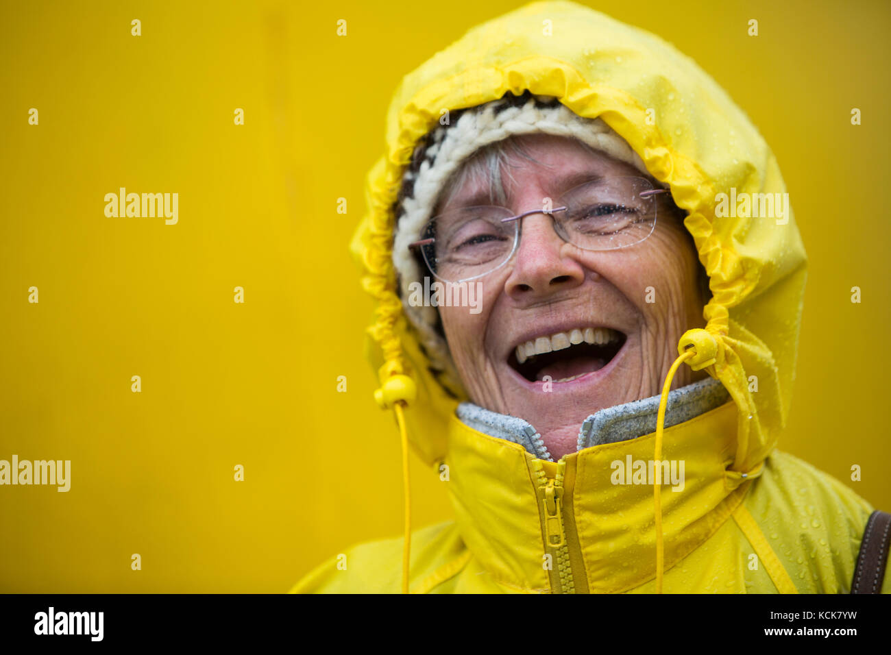 A happy, laughing senior citizen dressed up in her yellow rain slicker enjoys the stormy weather while aboard the - Stock Image