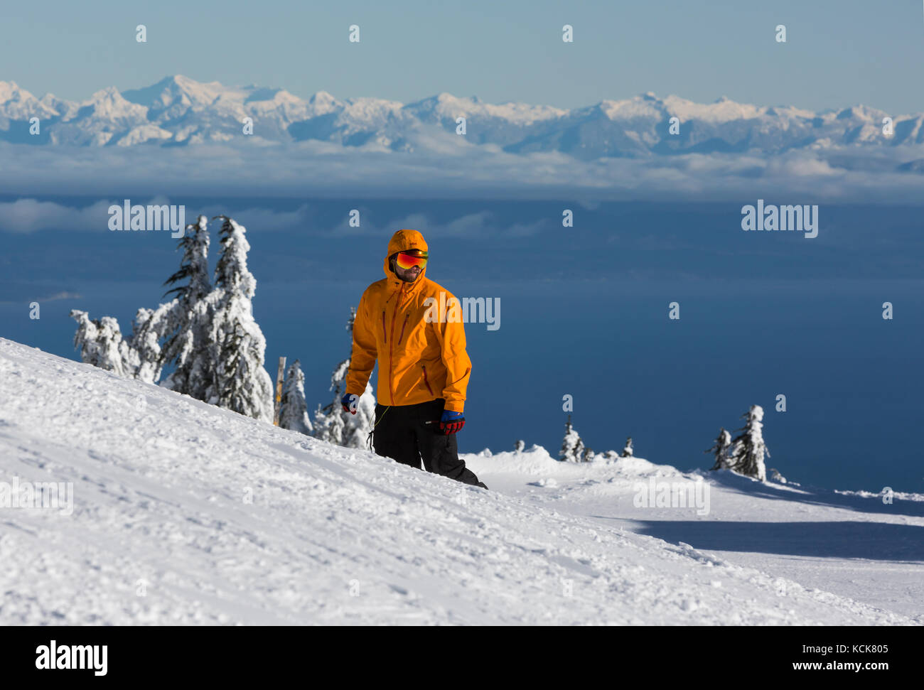 A colorful snowboarder on a ski run at Mt. Washington contrasts with a snowcapped Coast Range mountain scenic, Mt. - Stock Image
