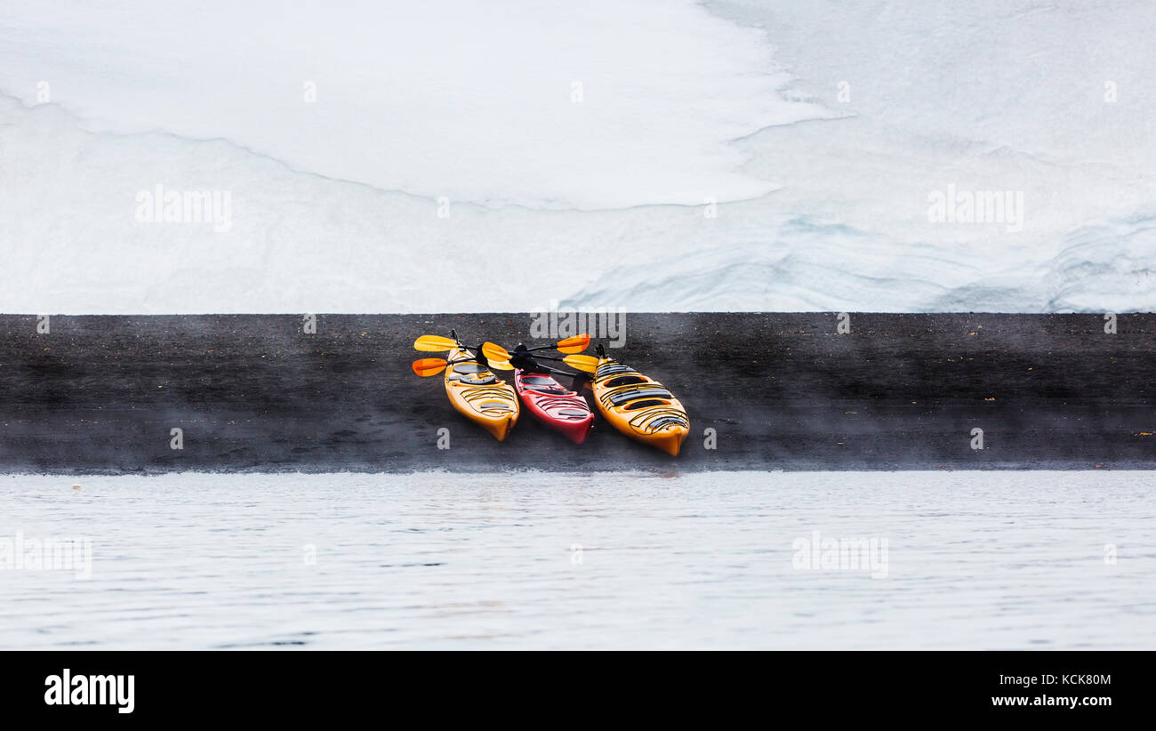 A white snowfield in the background contrasts with three Kayaks pulled up onto the black volcanic sands of Whaler's - Stock Image