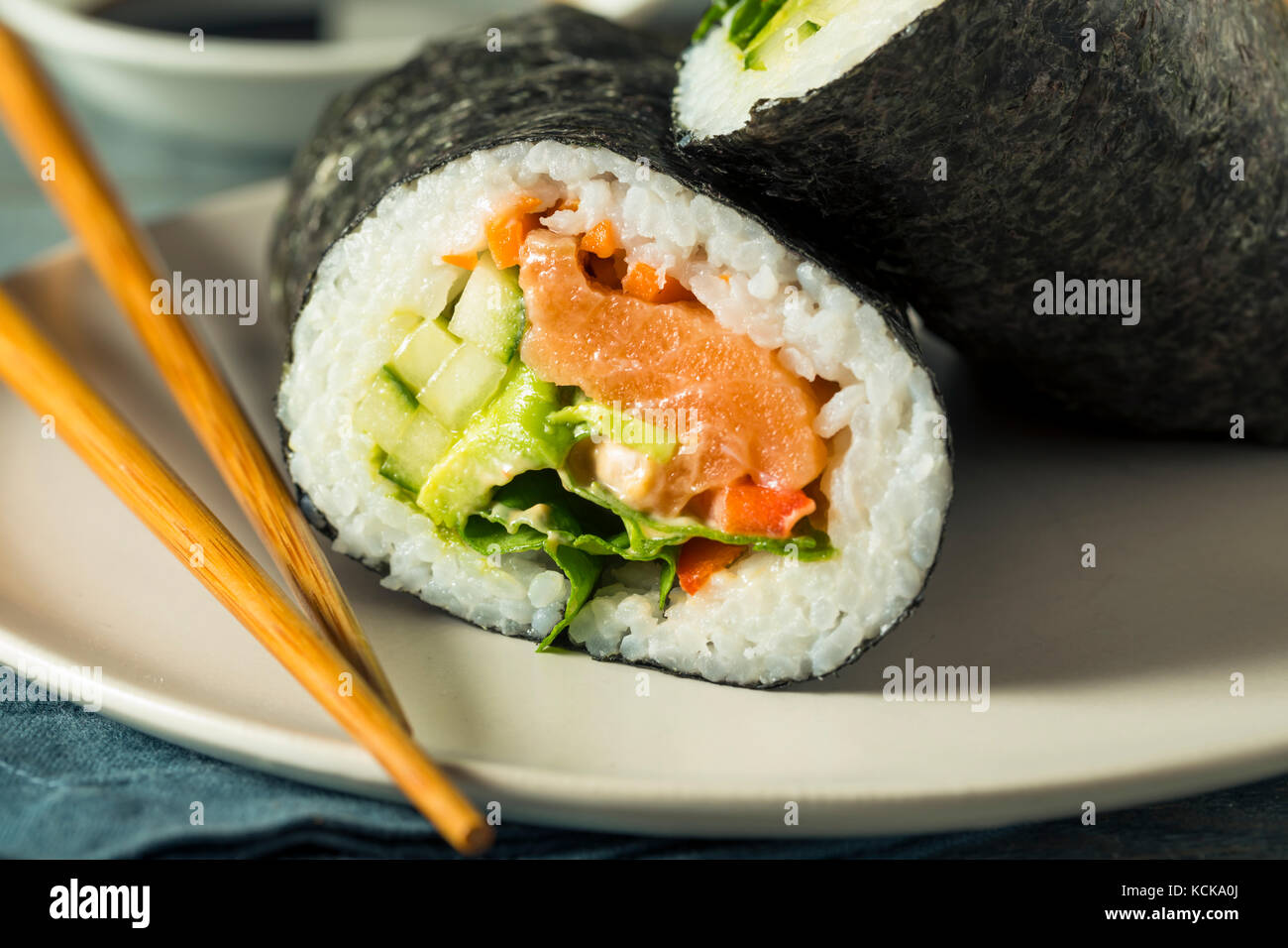 Raw Homemade Salmon Sushi Burrito with Seaweed Cucumber and Carrots - Stock Image