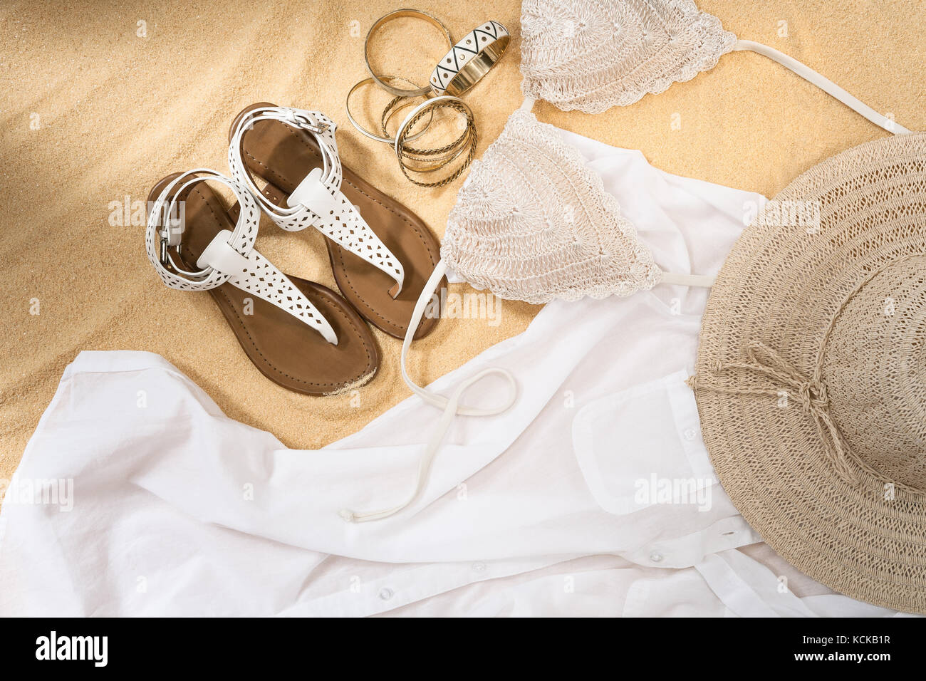 set of bright summer clothes for the beach on the golden sand - Stock Image