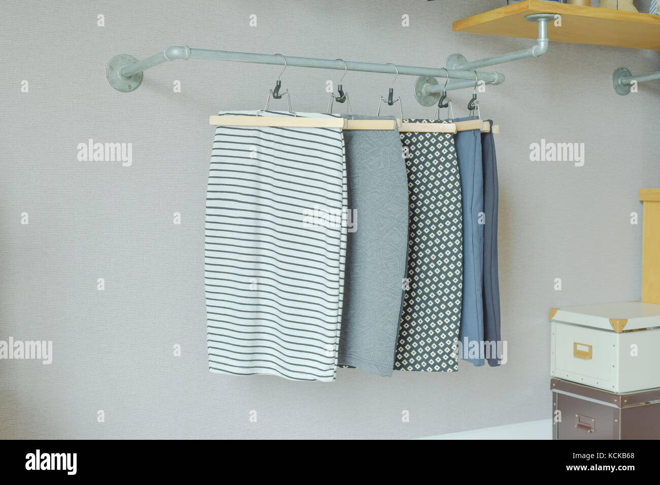 skirts hanging on industrial style clothes rail in walk in closet - Stock Image