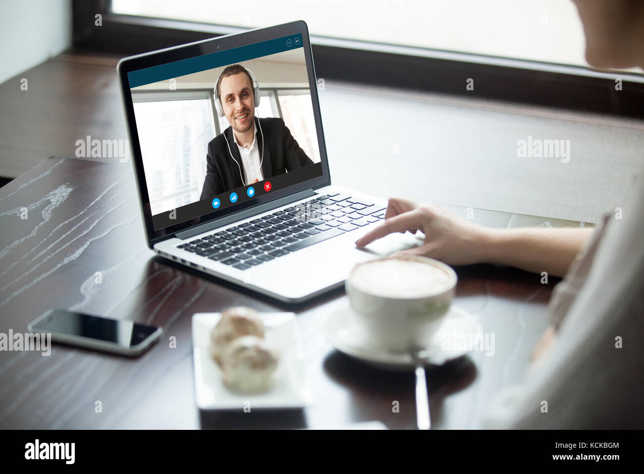 Woman talking to man in headphones via video call. Remote co-workers chatting, learning and exchanging foreign languages, - Stock Image