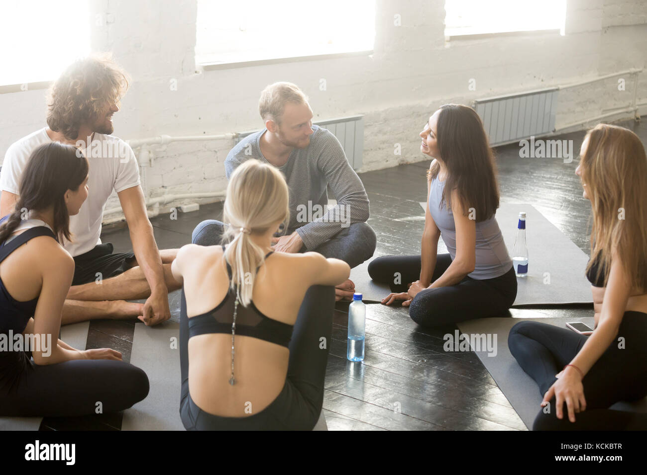 Group of sporty happy people sitting on the gym floor, students talking and resting after yoga class having an open Stock Photo
