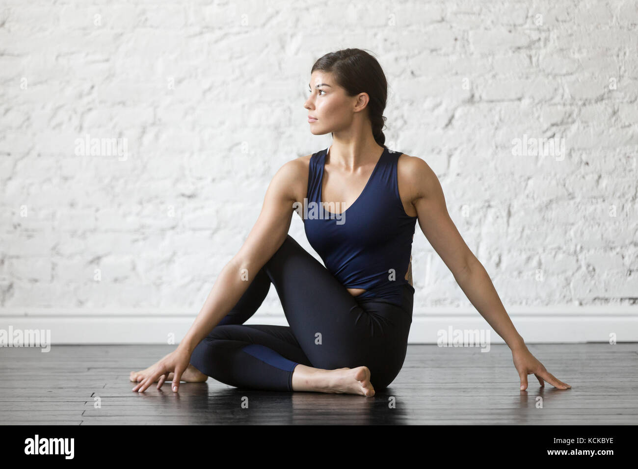 Young attractive woman practicing yoga, sitting in Ardha Matsyendrasana exercise, Half lord of the fishes pose, - Stock Image