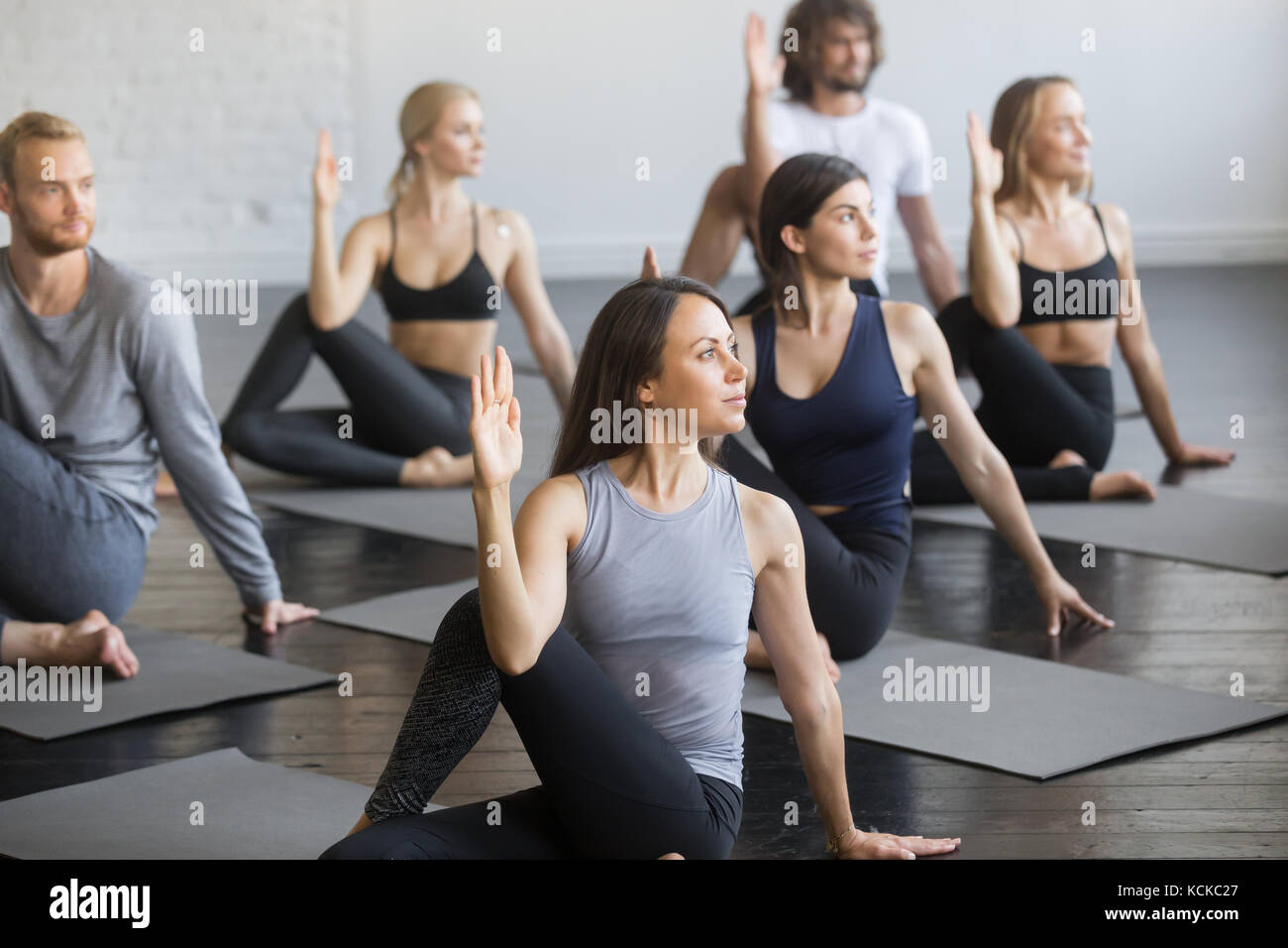 Group of young sporty people practicing yoga lesson with instructor, sitting in Half lord of the fishes exercise, - Stock Image